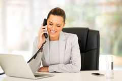 Businesswoman landline phone. Happy businesswoman using landline phone Stock Photography
