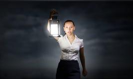 Businesswoman with lantern Stock Photos