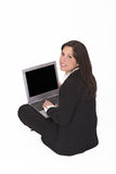 Businesswoman with laptop. Businesswoman sitting with a laptop in her lap and looking up back over the shoulder Stock Photography