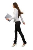 Businesswoman with laptop. A young businesswoman walking and holding a laptop, isolated on white background Royalty Free Stock Photos