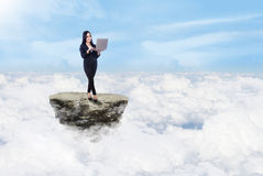 Businesswoman and laptop above clouds Royalty Free Stock Photo