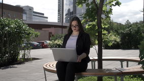 Businesswoman with laptop on bench. Confident modern businesswoman using laptop computer sitting on bench in city partk stock video footage