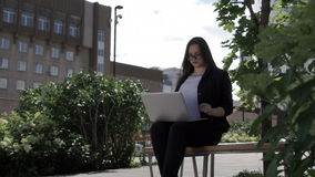 Businesswoman with laptop on bench. Confident modern businesswoman using laptop computer sitting on bench in city partk stock video