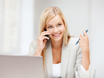 Businesswoman with laptop and cell phone Royalty Free Stock Photography