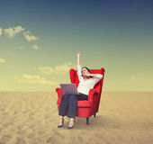 Businesswoman with laptop on chair working in desert Royalty Free Stock Photos