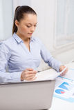 Businesswoman with laptop and charts in office Royalty Free Stock Image