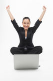 Businesswoman with laptop. Cheerful young businesswoman looking at the computer monitor and holding her arms raised while isolated on white Stock Photography