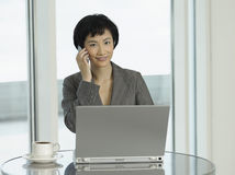 Businesswoman With Laptop And Coffee Using Cellphone Royalty Free Stock Image