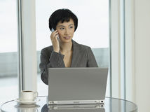 Businesswoman With Laptop And Coffee Using Cellphone Stock Images