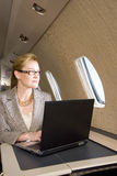 Businesswoman with laptop computer on aeroplane, looking out window Stock Image