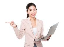 Businesswoman with laptop computer and finger point aside Stock Photos