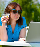 Businesswoman with laptop and glass of martini Stock Photo