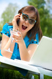 Businesswoman with laptop and glass of martini Royalty Free Stock Photos