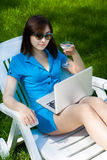 Businesswoman with laptop and glass of martini Stock Images