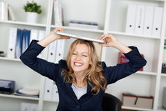 Businesswoman With Laptop On Head Clenching Teeth Stock Images