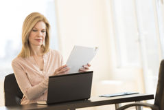 Businesswoman With Laptop Holding Resume In Office Royalty Free Stock Photo