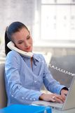 Businesswoman with laptop and landline phone Royalty Free Stock Image