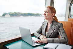 Trip of trader. Businesswoman with laptop looking through steaner window during her trip Royalty Free Stock Images