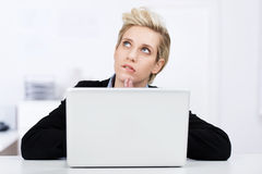 Businesswoman With Laptop Looking Up At Desk Stock Photo