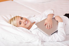 Businesswoman With Laptop Lying On Bed Stock Photography