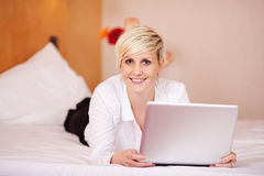 Businesswoman With Laptop While Lying On Bed Royalty Free Stock Photos