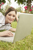 Businesswoman With Laptop Lying At Park Royalty Free Stock Images