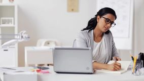 Businesswoman with laptop and notebook at office. Business, people and paperwork concept - smiling businesswoman with laptop computer and papers writing to stock video