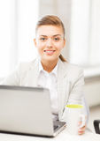 Businesswoman with laptop in office Stock Image