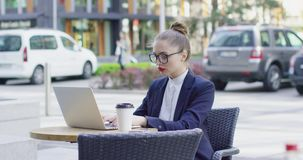 Businesswoman with laptop in outside cafe. Young stylish woman in formal clothing wearing makeup and glasses using laptop while sitting in cafe stock video footage