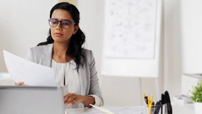 Businesswoman with laptop and papers at office