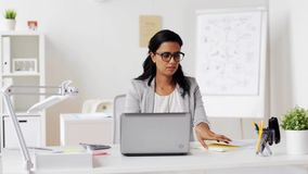 Businesswoman with laptop and papers at office stock footage