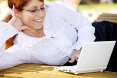 Businesswoman with laptop in the park Royalty Free Stock Image
