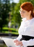Businesswoman with laptop in the park Royalty Free Stock Photos