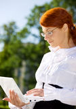 Businesswoman with laptop in the park Stock Image
