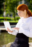 Businesswoman with laptop in the park Royalty Free Stock Photo