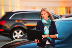 Fashion business woman using laptop on the car parking Stock Images