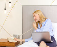 Businesswoman with laptop and phone in hotel room Royalty Free Stock Photography