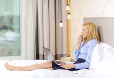 Businesswoman with laptop and phone in hotel room Stock Photo