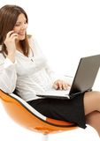 Businesswoman with laptop and phone in orange Royalty Free Stock Images