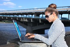 Businesswoman with laptop on quay Royalty Free Stock Photography