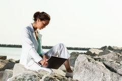 Businesswoman with laptop sitting on a beach Royalty Free Stock Images