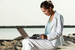 Businesswoman with laptop sitting on a beach Royalty Free Stock Photos