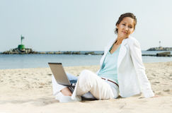 Businesswoman with laptop sitting on a beach Royalty Free Stock Image