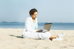 Businesswoman with laptop sitting on a beach Stock Image