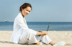 Businesswoman with laptop sitting on a beach Stock Photos