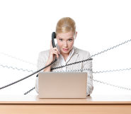 Businesswoman with laptop tied with phone cord Royalty Free Stock Photos