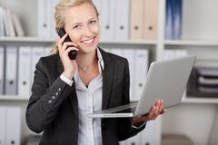 Businesswoman With Laptop Using Phone In Office Stock Photo