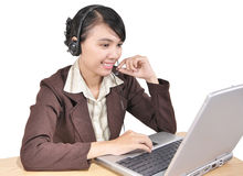Businesswoman with a laptop and wearing headphones. Young entrepreneurs are working with a laptop and wearing headphones, isolated on a white background Stock Image