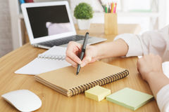 Businesswoman with laptop writing in notepad. Close up of businesswoman`s hands writing in spiral notepad placed on wooden desktop with blank laptop screen stock photo