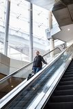 Businesswoman with large black bag and mobile phone descending on escalator. Stock Photos